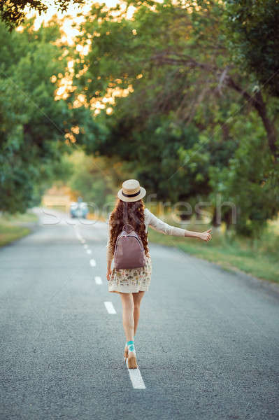 Girl with hat and backpack hitchhiking on the road Stock photo © artfotodima
