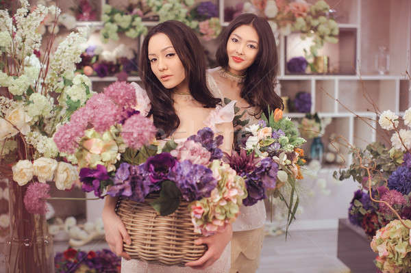 Beautiful asian women florists happy working in flower store with a lot of spring flowers Stock photo © artfotodima