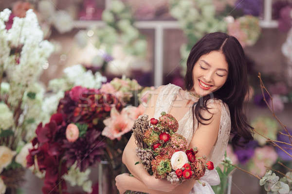 Stock photo: Beautiful asian woman florist in white dress with bouquet of flowers in hands in flower store