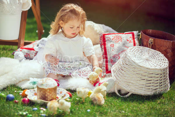 Child sits on a meadow around Easter decoration Stock photo © artfotodima