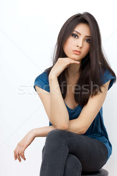 Annoyed asian woman sitting and lookin at camera on white background Stock photo © artfotodima