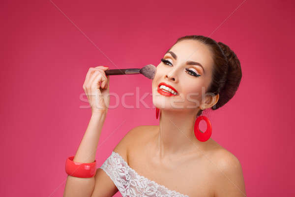 Smiling Woman with makeup brush. She is standing against a pink background. Stock photo © artfotodima
