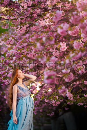 Beautiful young woman standing at blossoming tree in the garden Stock photo © artfotodima