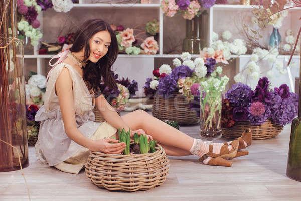Beautiful asian woman florist in lacy white dress in flower store Stock photo © artfotodima