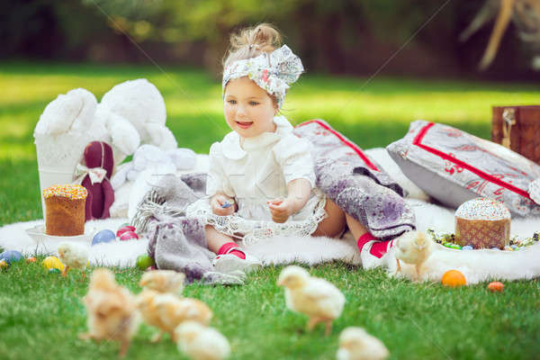 Happy child sits on a meadow around easter decoration Stock photo © artfotodima