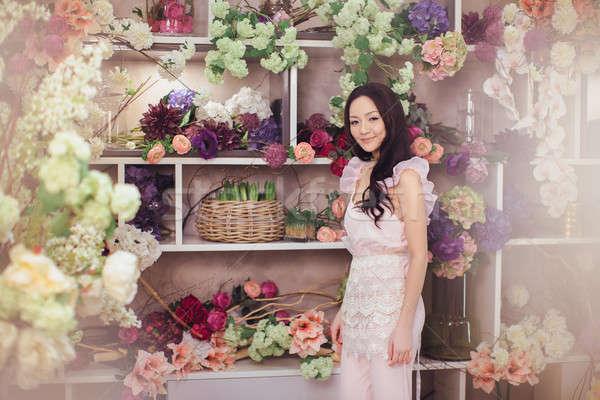 Gyönyörű ázsiai nő virágárus rózsaszín ruha Stock fotó © artfotodima