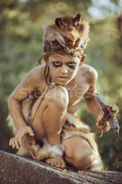 Caveman, manly boy with primitive weapon hunting outdoors. Ancient prehistoric warrior. Heroic movie Stock photo © artfotodima