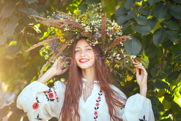 Beautiful girl in meadow in national suite Stock photo © artfotodima