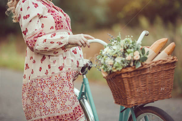 Stock photo: Pregnant belly against nature close-up. Woman retro French style with bicycle on a forest road