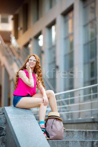 Kobieta posiedzenia ulicy mówić telefonu modny Zdjęcia stock © artfotodima