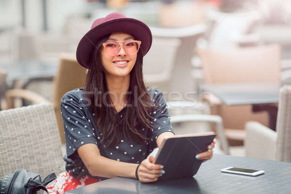 Asian young woman working with mobile phone and tablet computer in cofe shop. Stock photo © artfotodima