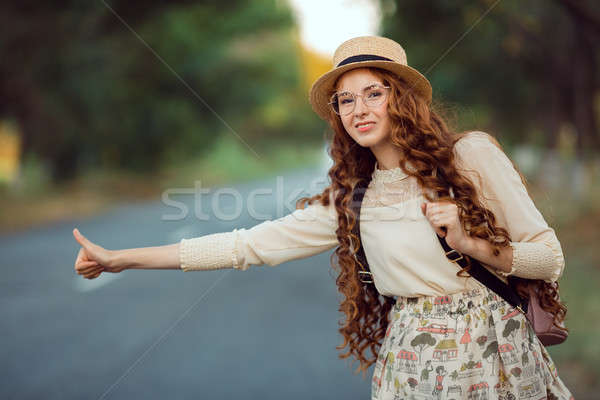 Stock photo: Girl with hat and backpack hitchhiking on the road