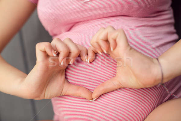 Pregnant Woman holding her hands in heart shape on baby bump. Stock photo © artfotodima