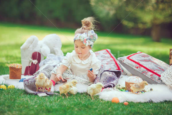 Happy child sits on a meadow looks to Easter decoration Stock photo © artfotodima