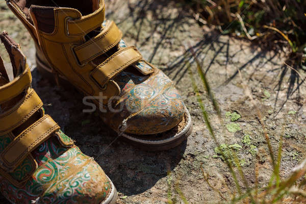 Old tourists boots on stone near mountain stream Stock photo © artfotodima