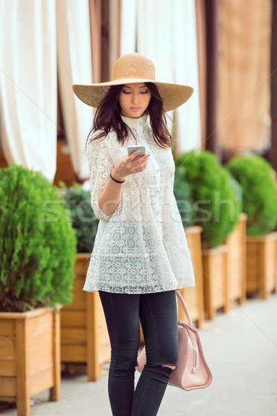 Stylish young asian girl with smartphone on city street against cafe facade Stock photo © artfotodima