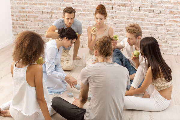 Group of young multi-ethnic beautiful couples sitting together and smiling talking eating Stock photo © artfotodima