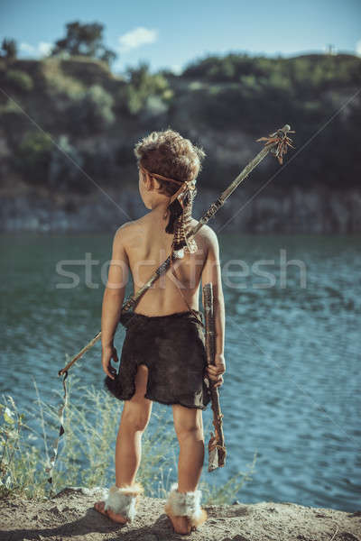 Stock photo: Caveman, manly boy with stone axe and bow hunting