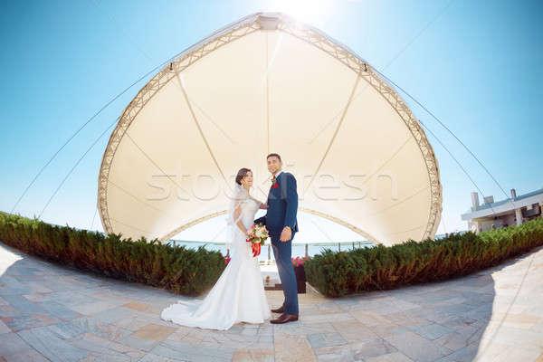 Jonge bruiloft paar permanente buitenshuis genieten Stockfoto © artfotodima