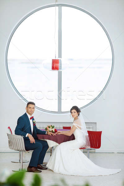 Bride and groom sitting in indoors cafe Stock photo © artfotodima