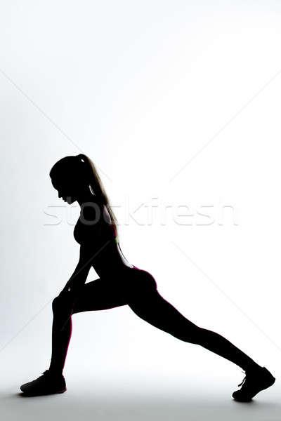 Fitness woman silhouette doing stretching exercise. Stock photo © artfotodima