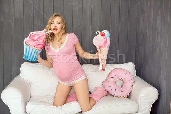Pregnant woman with toys of ice cream posing indoors at home. Heath care and food consept. Stock photo © artfotodima