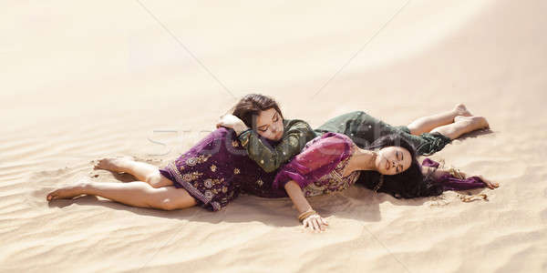 Women thirsty laying in a desert. Lost in desert durind sandshtorm Stock photo © artfotodima