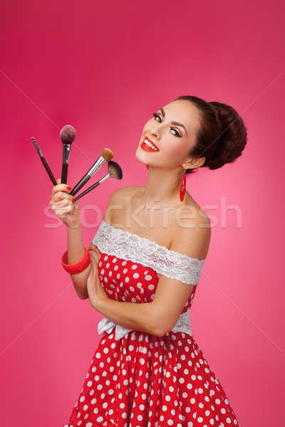 Smiling Woman with makeup brushes. She is standing against a pink background. Stock photo © artfotodima