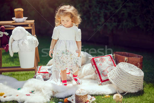 Happy child plays on a meadow around Easter decoration Stock photo © artfotodima