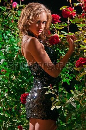 an attractive woman standing among the rose bushes Stock photo © artfotoss
