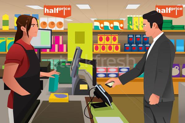 Człowiek kasjer telefonu sklep spożywczy dziewczyna Zdjęcia stock © artisticco