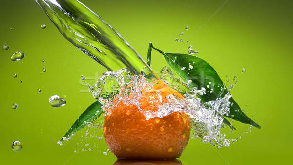 Tangerine with green leaves and water splash on green Stock photo © artjazz