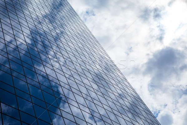 Blue office building with clouds reflection Stock photo © artjazz