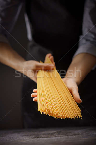 A bunch of spaghetti in the hands of a woman on a dark background. The concept of Italian food Stock photo © artjazz