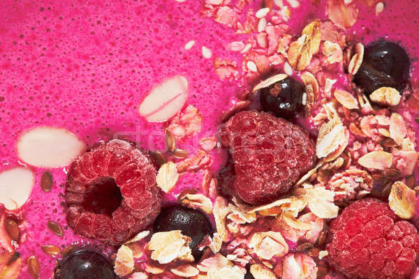 Smoothie topped with berries and granola close up Stock photo © artjazz