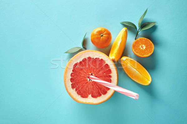 Citrus juice from orange, mandarin and grapefruit on a blue paper background top view Stock photo © artjazz