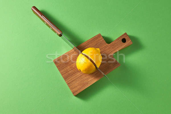 A sharp steel knife is cut by a yellow organic lemon in half on a wooden cutting board on a green ba Stock photo © artjazz