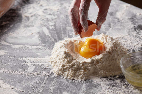 A woman holds an egg shell against a background of flour with yolks. Preparation of the dough Stock photo © artjazz
