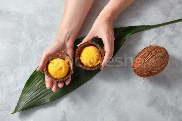 Female hands hold two halves of coconut shell with balls of yellow mango ice cream over the green tr Stock photo © artjazz