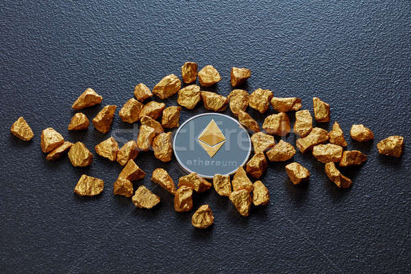Gold nuggets and Etereum coin on a black concrete background. Business concept. Stock photo © artjazz