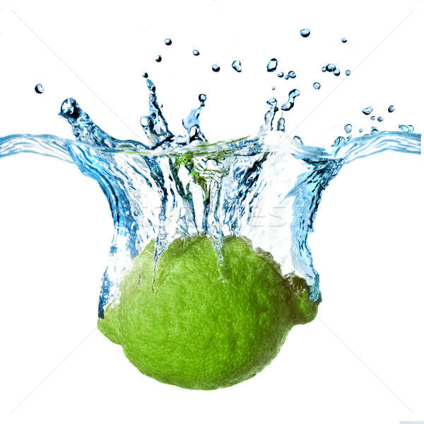 Fresh lime dropped into water with splash isolated on white Stock photo © artjazz