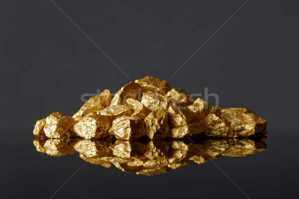 Mound of gold nuggets on a black reflective surface background Stock photo © artjazz