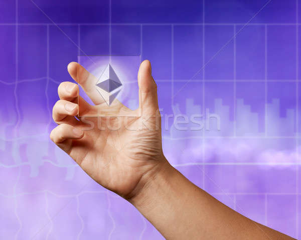 Icon of etereum on a transparent digital screen on the ultraviolet background of the city Stock photo © artjazz