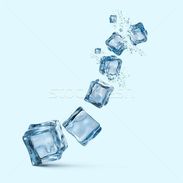 ice cubes with water splashes isolated on blue background Stock photo © artjazz