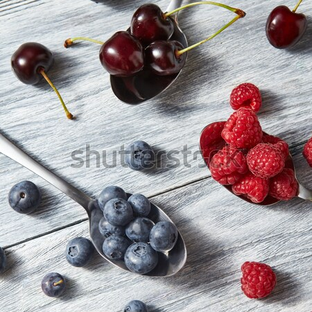 Freshly picked raspberry and blueberry in a spoons on a gray wooden background. Top view. Stock photo © artjazz
