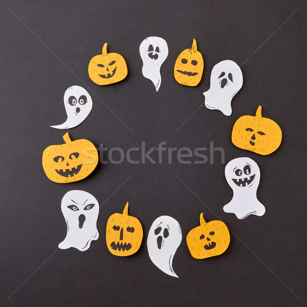 Round frame of handmade horrible smiling spirits and ghosts and laughing pumpkin on a black paper ba Stock photo © artjazz