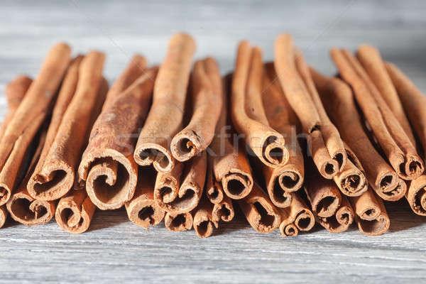 Cinnamon sticks isolated on white wooden table Stock photo © artjazz