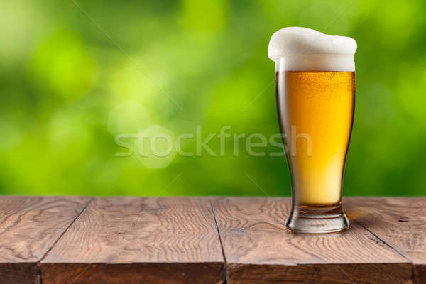Beer in glass on wooden table against green  Stock photo © artjazz