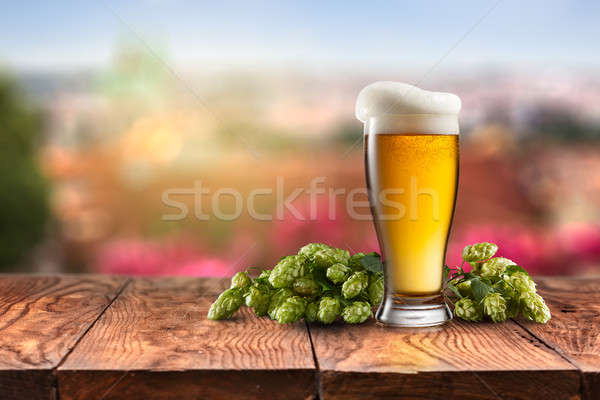 glass with Beer and hop on a wooden table Stock photo © artjazz