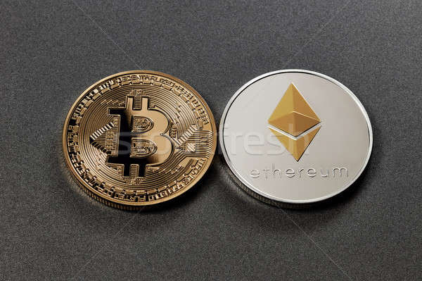 Two coins bitcoin and ethereum on a dark background. Business concept Stock photo © artjazz